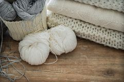 Un panier tissé avec le fil blanc et gris pour le tricotage et les aiguilles de tricotage Chandails et fil blancs pour le plan ra Image stock