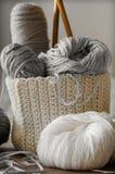 Un panier tissé avec le fil blanc et gris pour le tricotage et les aiguilles de tricotage Chandails et fil blancs pour le plan ra Photographie stock libre de droits