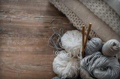 Un panier tissé avec le fil blanc et gris pour le tricotage et les aiguilles de tricotage Chandails et fil blancs pour le plan ra Photo stock