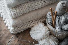 Un panier tissé avec le fil blanc et gris pour le tricotage et les aiguilles de tricotage Chandails et fil blancs pour le plan ra Photos libres de droits