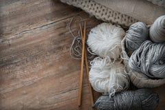 Un panier tissé avec le fil blanc et gris pour le tricotage et les aiguilles de tricotage Chandails et fil blancs pour le plan ra Photographie stock