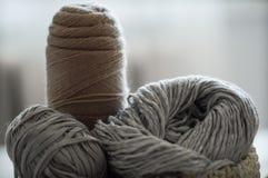 Un panier tissé avec le fil blanc et gris pour le tricotage et les aiguilles de tricotage Chandails et fil blancs pour le plan ra Photos stock