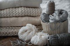 Un panier tissé avec le fil blanc et gris pour le tricotage et les aiguilles de tricotage Chandails et fil blancs pour le plan ra Image libre de droits
