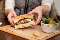 Un panino di bistecca sul pane di focaccia con un'insalata laterale fotografie stock