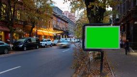 Un panneau d'affichage avec un écran vert sur un fond de circulation urbaine d'automne avec la longue exposition Laps de temps banque de vidéos