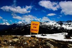Un panneau d'avertissement de rester sur la route tout en augmentant une montagne photo libre de droits