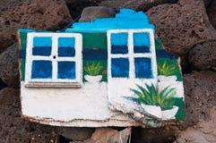 Un panneau en bois avec les fenêtres peintes accrochant sur les roches noires Images stock