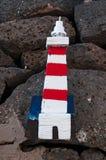 Un panneau en bois avec un phare accrochant sur les roches noires Photographie stock