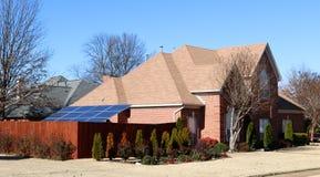 Un panneau solaire actionne une maison suburbaine de classe moyenne photographie stock
