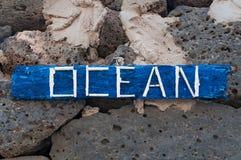 un pannello di legno con l'oceano scritto che appende sulle rocce nere Immagine Stock