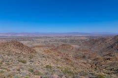 Un panorama del desierto con formaciones de roca y cadena de montaña distante en horizonte imagenes de archivo