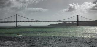Un panorama della possibilità remota di 25 de Abril Bridge a Lisbona Fotografia Stock