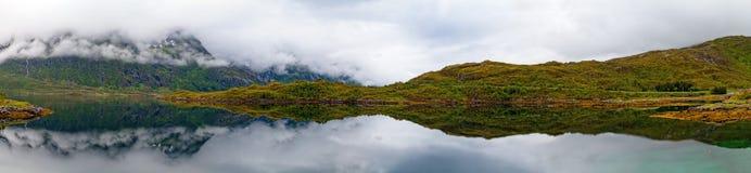 Un panorama di un lago, di una montagna e di una collina in nebbioso Immagini Stock