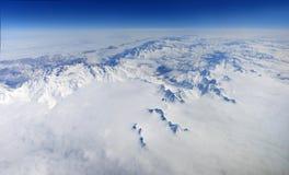 Un panorama hermoso de montañas coronadas de nieve con las nubes fotografía de archivo libre de regalías