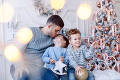 Un papá de a con sus gemelos de dos hijos delante del árbol de navidad que abraza y que se divierte Concepto de familia grande fotografía de archivo libre de regalías