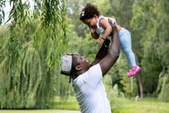 Un papá que detiene a su hija Padre feliz que juega con la hija en el parque foto de archivo libre de regalías