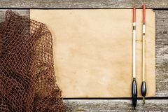 Un papel viejo, una red de pesca y una pesca flotan en un tabl de madera fotografía de archivo libre de regalías