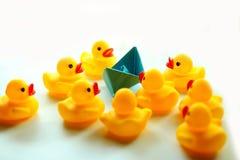 Un papier bleu de bateau et des canards en caoutchouc jaunes photos stock