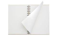Un papier ouvert de cahier s'est enroulé Photos stock
