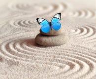 Un papillon vif bleu sur une pierre de zen avec des modèles de cercle dans le sable de grain images stock