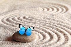 Un papillon vif bleu sur une pierre de zen avec des modèles de cercle dans le sable de grain photo libre de droits