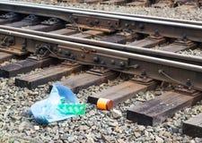 Un paquet avec des déchets sur le chemin de fer jeté de la fenêtre du train par des passagers, pollution, des débris et le chemin photographie stock