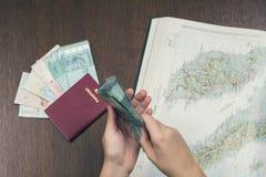 Un paquet d'argent malaisien dans les mains femelles sur la carte de la Malaisie et le passeport de voyage sur le fond Photo stock