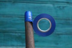 Un paquet de bande d'isolation bleue enroulent sur un tuyau rouillé sur un fond vert image libre de droits
