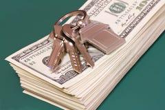 Un paquet de billets de banque et de clés sur une table verte Image stock
