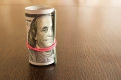 Un paquet de tordre 100 billets d'un dollar Sur une table en bois Photographie stock