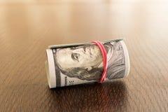 Un paquet de tordre 100 billets d'un dollar Sur une table en bois Images stock