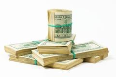 Un paquet tordu de 100 billets d'un dollar se tient sur des paquets de dollars Image stock