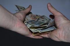 Un paquet tordu de 100 factures du dollar et d'euro dans une main sur un fond noir Photos stock