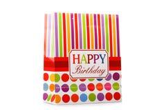 Un paquete colorido con las rayas rojas, amarillas y rosadas y cumpleaños del significado un feliz aislados en un fondo blanco fotografía de archivo