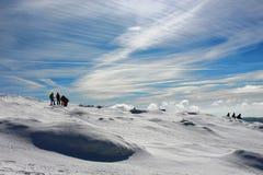 Un paquete de caminantes que caminan abajo de la cumbre en un día soleado del invierno, montañas de Montseny, Barcelona del pico  Foto de archivo