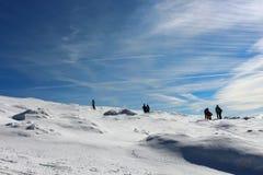 Un paquete de caminantes que caminan abajo de la cumbre en un día soleado del invierno, montañas de Montseny, Barcelona del pico  Fotografía de archivo libre de regalías