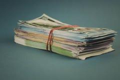 Un paquete de dinero atado con una goma en un fondo azul fotos de archivo