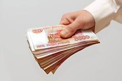 Un paquete de dinero en la mano Imágenes de archivo libres de regalías