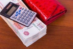 Un paquete de dinero, la cartera de cuero roja y la calculadora están en la tabla Imagen de archivo libre de regalías