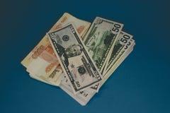un paquete de las rublos rusas y de los d?lares dos tacos de dinero en un fondo azul riqueza de la oportunidad ?xito foto de archivo