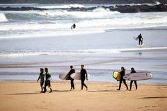 Un paquete de personas que practica surf que disfrutan de su tiempo en la playa de San Lorenzo durante una mañana soleada de Pasc fotografía de archivo libre de regalías