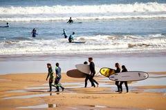 Un paquete de personas que practica surf que disfrutan de su tiempo en la playa de San Lorenzo durante una mañana soleada de Pasc fotos de archivo libres de regalías
