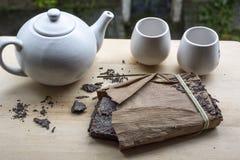 Un paquete de té chino negro con la tetera blanca y dos tazas fotos de archivo libres de regalías