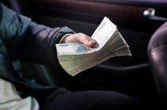 Un paquete grande de dinero ruso se exprime en su mano fotografía de archivo