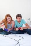 Un par adolescente emocionado que juega a los juegos video Imagen de archivo libre de regalías