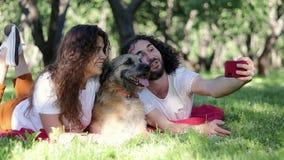 Un par alegre joven que toma un selfie en el parque con su perro lanudo almacen de metraje de vídeo