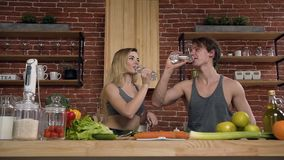 Un par apto feliz está preparando la comida en la cocina que hace clic con las botellas y el agua potable en la cocina en casa metrajes
