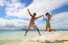 Un par asiático que salta en una playa Imagen de archivo