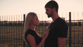 Un par atractivo en abrazo del amor y disfrutar de un momento íntimo junto, contra la puesta del sol o la salida del sol almacen de metraje de vídeo