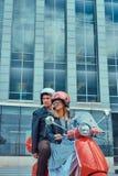 Un par atractivo, un hombre hermoso y el montar femenino atractivo junto en una vespa retra roja en una ciudad foto de archivo